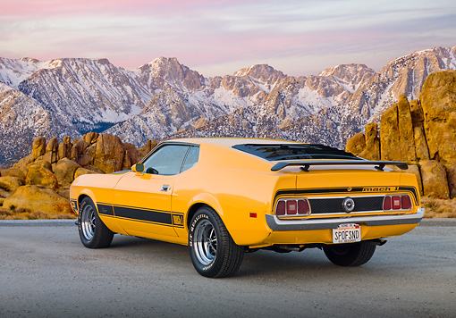MST 01 BK0017 01 © Kimball Stock 1973 Ford Mustang Mach 1 Grabber Yellow 3/4 Rear View On Pavement By Snowy Mountain Peaks