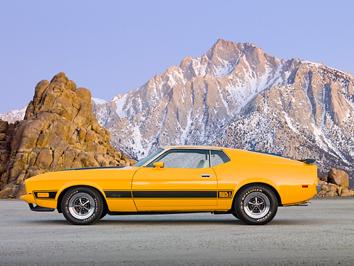 MST 01 BK0018 01 © Kimball Stock 1973 Ford Mustang Mach 1 Grabber Yellow Profile View On Pavement By Snowy Mountain Peaks