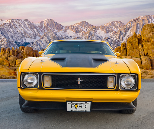 MST 01 BK0019 01 © Kimball Stock 1973 Ford Mustang Mach 1 Grabber Yellow Front View On Pavement By Snowy Mountain Peaks