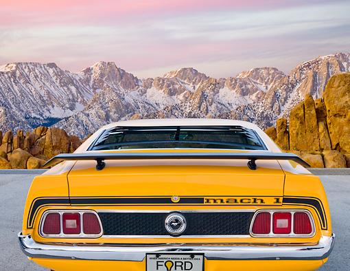 MST 01 BK0020 01 © Kimball Stock 1973 Ford Mustang Mach 1 Grabber Yellow Rear View On Pavement By Snowy Mountain Peaks