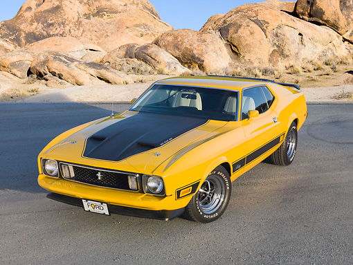 MST 01 BK0021 01 © Kimball Stock 1973 Ford Mustang Mach 1 Grabber Yellow 3/4 Front View On Pavement By Boulders