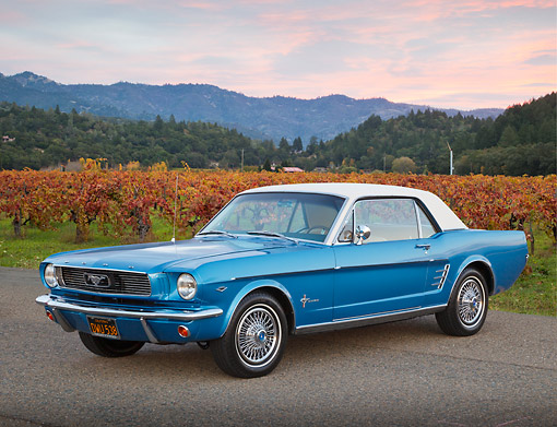 MST 01 BK0063 01 © Kimball Stock 1966 Ford Mustang Blue With White Top 3/4 Front View On Pavement By Vineyard At Dusk