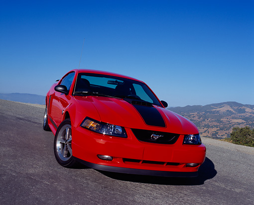 MST 01 RK0663 02 © Kimball Stock 2004 Ford Mustang Mach 1 40th Anniversary Orange And Black 3/4 Front View On Pavement Hill Blue Sky