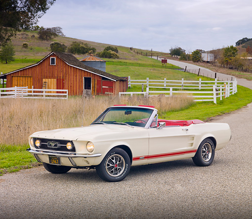 MST 01 RK1222 01 © Kimball Stock 1967 Ford Mustang GTA Convertible White 3/4 Front View On Pavement By Barn