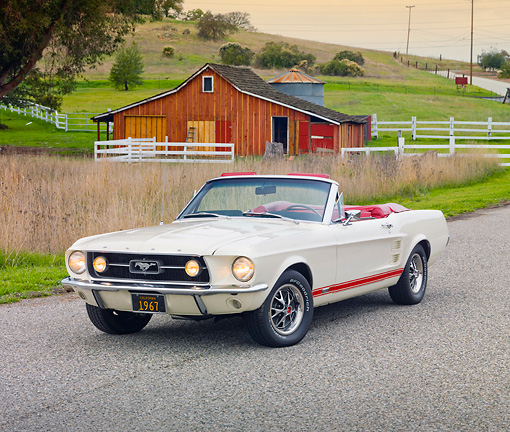 MST 01 RK1223 01 © Kimball Stock 1967 Ford Mustang GTA Convertible White 3/4 Front View On Pavement By Barn