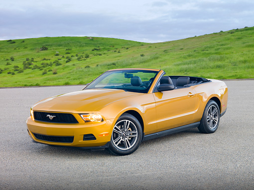 MST 01 RK1235 01 © Kimball Stock 2010 Ford Mustang Gold 3/4 Front View On Pavement By Grassy Hills