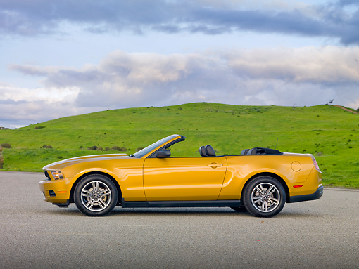 MST 01 RK1238 01 © Kimball Stock 2010 Ford Mustang Gold Profile On Pavement By Grassy Hills
