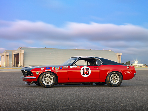 MST 01 RK1327 01 © Kimball Stock 1969 Ford Mustange Boss 302 Trans Am Race Car Red, White And Black Profile View On Pavement By Hangars At Dusk