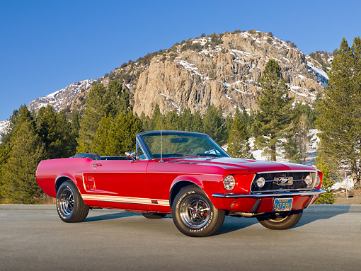 MST 01 RK1383 01 © Kimball Stock 1967 Ford Mustang GTA Convertible Red 3/4 Front View On Pavement By Snowy Mountainside