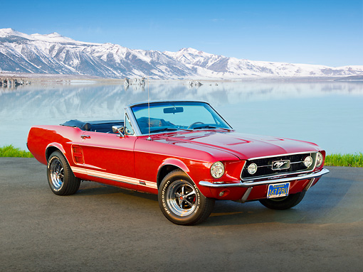 MST 01 RK1385 01 © Kimball Stock 1967 Ford Mustang GTA Convertible Red 3/4 Front View On Pavement By Water And Snowy Mountain Peaks