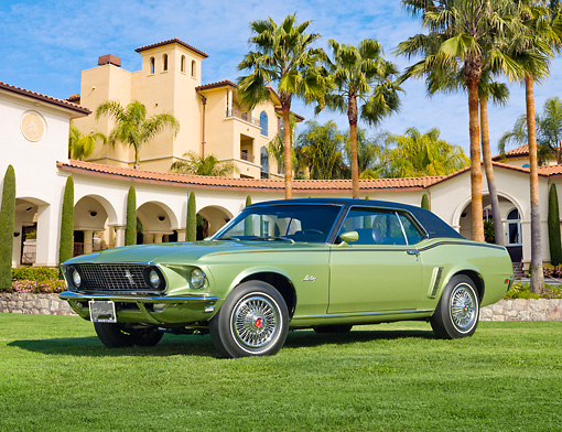 MST 01 RK1447 01 © Kimball Stock 1969 Ford Mustang Grande Lime Gold 3/4 Front View On Grass By Building And Palm Trees