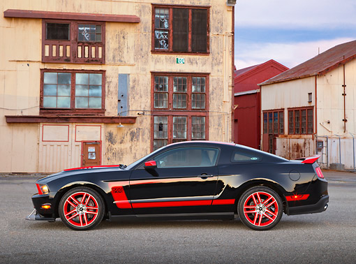 MST 01 RK1644 01 © Kimball Stock 2012 Ford Mustang Boss 302 Laguna Seca Edition Black And Red Profile View On Pavement By Old Buildings