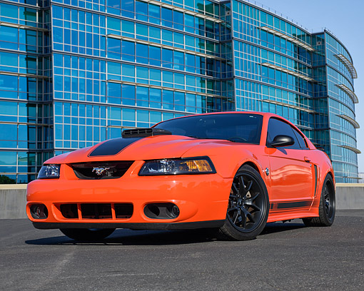 MST 01 RK1666 01 © Kimball Stock 2004 Ford Mustang Mach 1 Orange 3/4 Front View On Pavement By Building