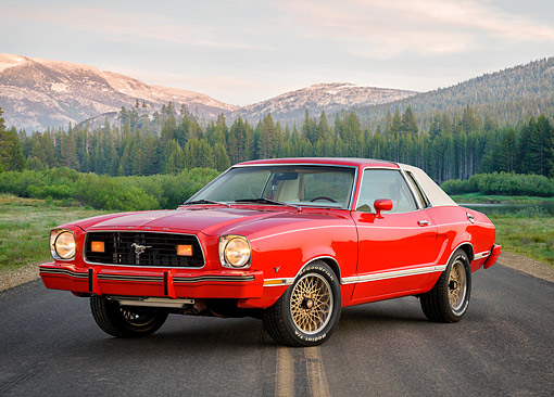MST 01 RK1688 01 © Kimball Stock 1978 Ford Mustang II Ghia Red 3/4 Front View On Road By Trees