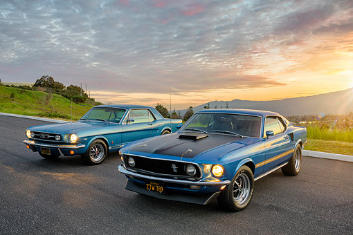MST 01 RK1690 01 © Kimball Stock 1969 Ford Mustang Mach I Cobra Jet 428 Blue And 1966 Ford Mustang GT 289 Blue 3/4 Front View On Pavement By Mountains