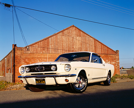 MST 01 RK0117 02 © Kimball Stock 1965 White Black Stripe Ford Mustang GT Fastback Low 3/4 Front On Pavement By Brick Building Blue Sky