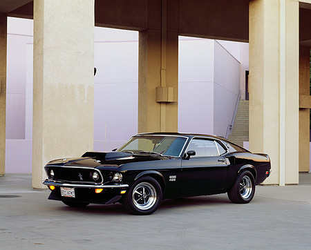 MST 01 RK0262 04 © Kimball Stock 1969 Mustang Boss 429 Black Side 3/4 View On Pavement By Pillars Parking Lights On