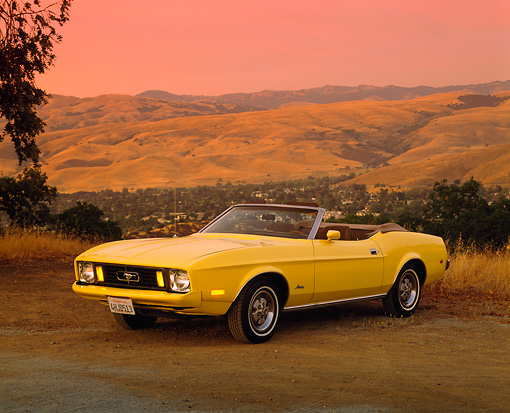 MST 01 RK0527 04 © Kimball Stock 1973 Ford Mustang Convertible Yellow 3/4 Front View On Dirt Dry Grass Hills Background Red Sky