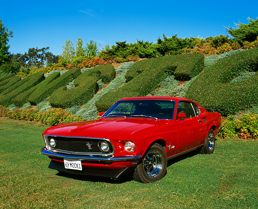 MST 01 RK0540 04 © Kimball Stock 1969 Mustang Fastback With Mach 1 Modifications Red 3/4 Front View On Grass By Plants