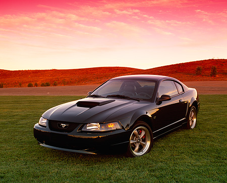 MST 01 RK0547 03 © Kimball Stock 2001 Ford Mustang Bullet Green 3/4 Front View On Grass Hills Red Sky