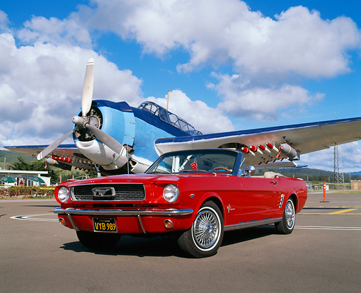 MST 01 RK0562 03 © Kimball Stock 1966 Ford Mustang Convertible Red Low 3/4 Front View On Pavement By Airplane Cloudy Sky