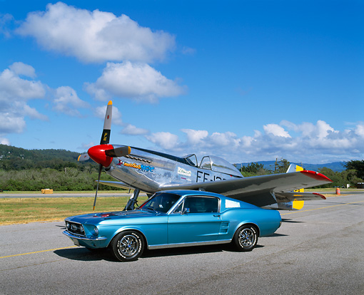 MST 01 RK0566 01 © Kimball Stock 1965 Ford Mustang Fastback Aqua 3/4 Side View On Pavement By Airplane Cloudy Blue Sky