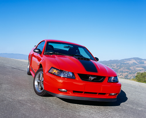 MST 01 RK0663 04 © Kimball Stock 2004 Ford Mustang Mach 1 40th Anniversary Orange And Black 3/4 Front View On Pavement Hill Blue Sky