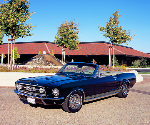MST 01 RK0702 03 © Kimball Stock 1967 Ford Mustang GTA Convertible Black 3/4 Front View On Pavement By Building