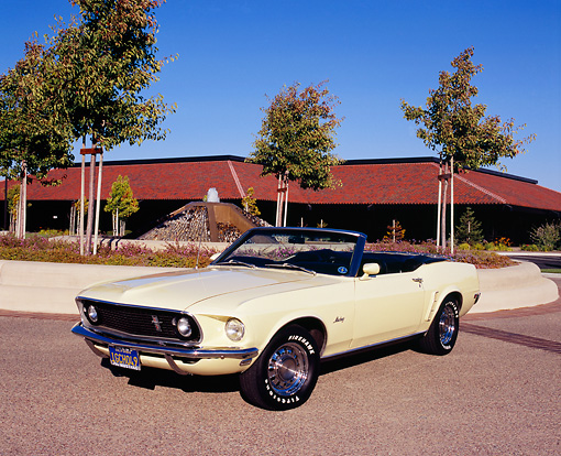 MST 01 RK0719 01 © Kimball Stock 1969 Ford Mustang Convertible Yellow 3/4 Front View On Pavement By Building And Trees