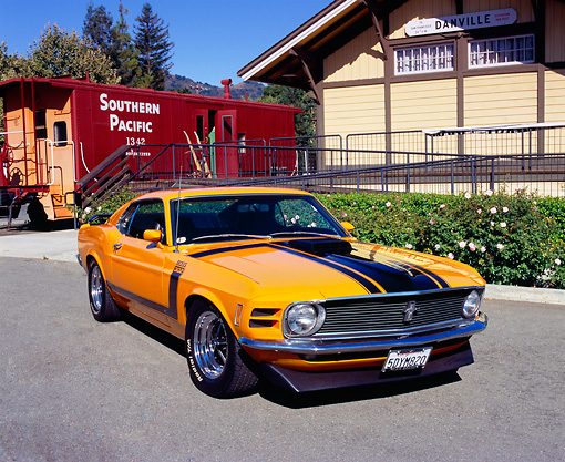 MST 01 RK0725 03 © Kimball Stock 1970 Ford Mustang Boss 302 Orange Black Stripes 3/4 Front View On Pavement By Train