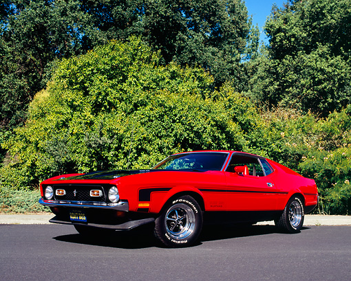 MST 01 RK0728 02 © Kimball Stock 1971 Ford Mustang Boss 351 Red Black Stripes Low 3/4 Side View On Pavement By Bushes