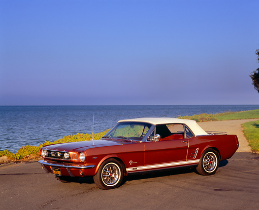 MST 01 RK0767 02 © Kimball Stock 1966 Ford Mustang Convertible Amberglo 3/4 Side View On Pavement By Water