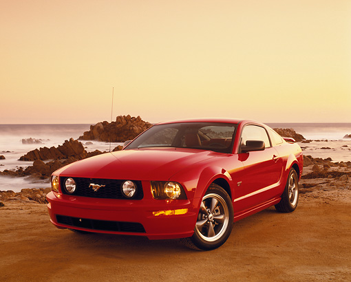 MST 01 RK0812 01 © Kimball Stock 2005 Ford Mustang GT Coupe Red 3/4 Front View On Sand By Rocks And Ocean Filtered