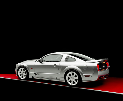 MST 02 RK0059 09 © Kimball Stock 2005 Ford Saleen Mustang Supercharged Silver 3/4 Rear View On Red Floor Gray Line Studio