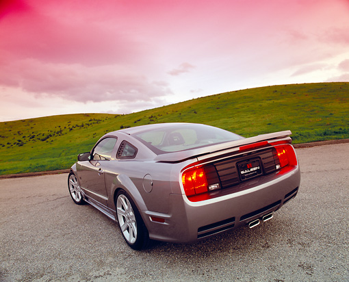 MST 02 RK0065 01 © Kimball Stock 2005 Ford Saleen Mustang Supercharged Silver 3/4 Rear View On Pavement By Grass Hills