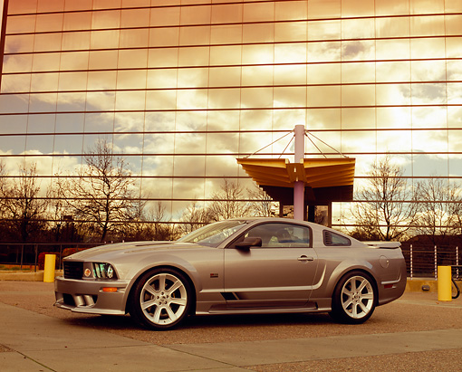 MST 02 RK0073 05 © Kimball Stock 2005 Ford Saleen Mustang Supercharged Silver 3/4 Side View On Pavement By Glass Building Filtered