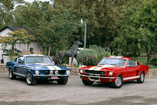 MST 03 RK0093 01 © Kimball Stock 1967 Ford Mustang Shelby GT500 Blue And 1966 Shelby GT350 Red 3/4 Front View On Pavement By Horse Statue