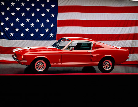MST 03 RK0012 01 © Kimball Stock 1967 Ford Shelby Mustang GT500 Red White Stripe 3/4 Side On Red Line Headlights On American Flag
