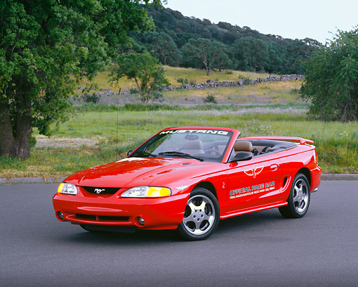 MST 04 RK0009 04 © Kimball Stock 1994 Ford Mustang Cobra Convertible Indy Racing Car Red 3/4 Front View On Pavement Trees