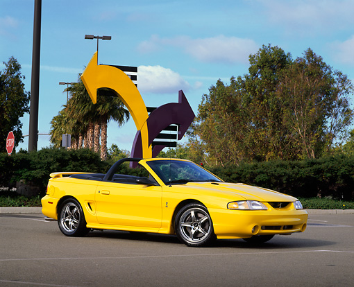 MST 04 RK0010 04 © Kimball Stock 1998 Ford Mustang Cobra Yellow 3/4 Front View On Pavement By Arrows Blue Sky Trees