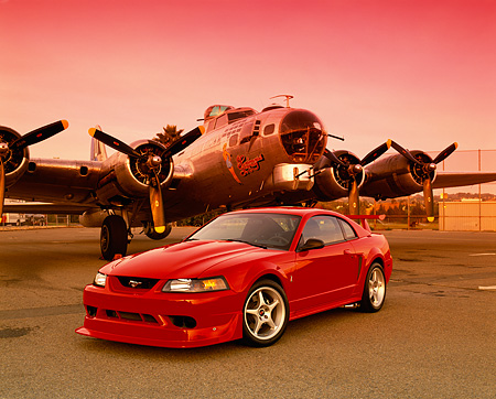 MST 04 RK0030 01 © Kimball Stock 2000 Ford Mustang Cobra R Red 3/4 Front View On Pavement By Plane Red Sky