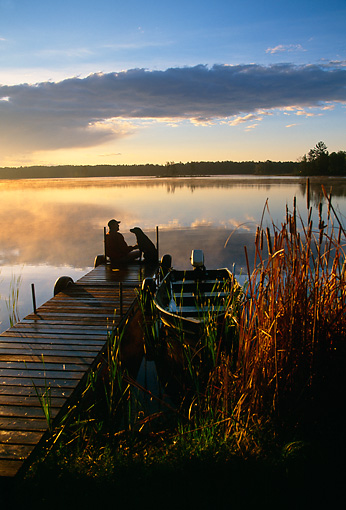 PEO 02 DB0002 01 © Kimball Stock Fisherman And Labrador Retriever Sitting On Dock Watching Sunset At Lake