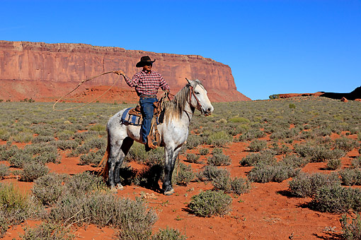 PEO 04 AC0004 01 © Kimball Stock Navajo Cowboy Swinging Lasso While Riding Mustang In Monument Valley, Utah, USA