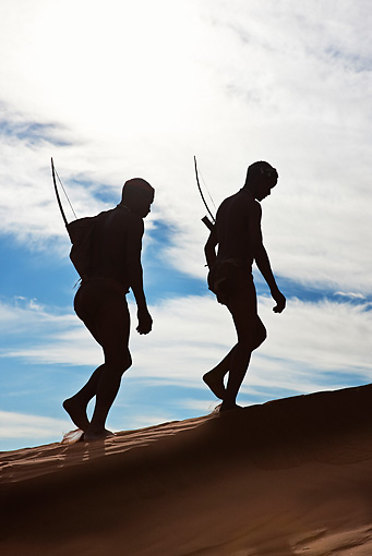 PEO 08 MH0005 01 © Kimball Stock Silhouette Of Two San Hunters Walking With Traditional Bow And Arrow Namibia