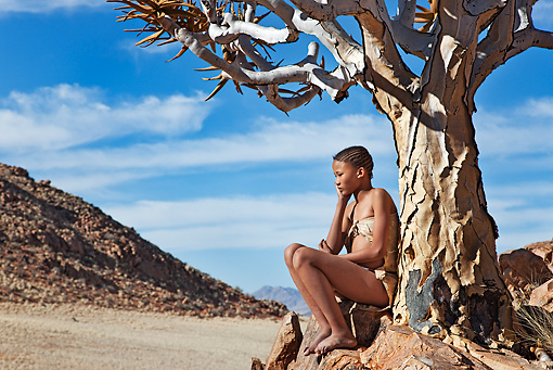 PEO 08 MH0013 01 © Kimball Stock Young San Girl Leaning Against Quiver Tree Namibia