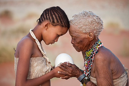PEO 08 MH0016 01 © Kimball Stock Elderly San Woman Offering Ostrich Egg As Gift To Young Girl For Making Jewelry