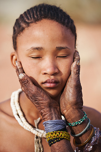 PEO 08 MH0019 01 © Kimball Stock Elderly San Woman's Hands Embracing Young Girl's Face Namibia