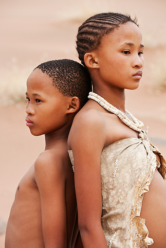 PEO 08 MH0021 01 © Kimball Stock Portrait Of San Brother And Sister Standing Back To Back Namibia