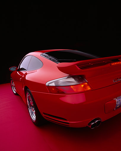 POR 03 RK0132 10 © Kimball Stock 2003 Porsche Turbo X50 Red Close Up Wide Angle 3/4 Rear View Shot On Red Floor Studio