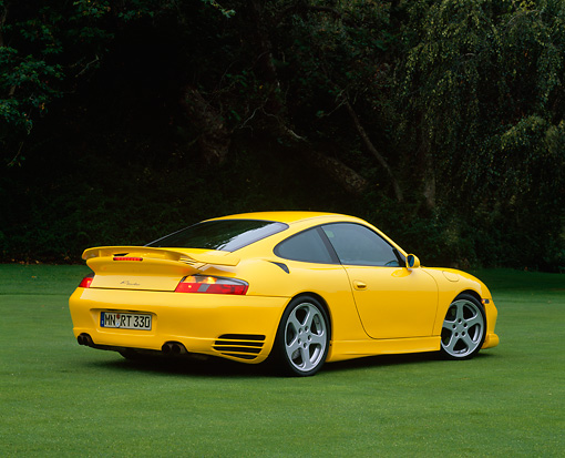 POR 03 RK0130 07 © Kimball Stock 2001 Porsche R Turbo Yellow Rear 3/4 View On Grass Trees Background